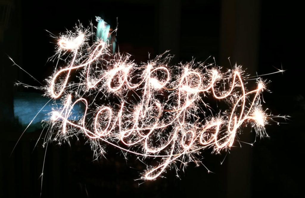 Happy new year written in flawless sparkler cursive, indicative of artist being a wizard or loser.